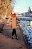Capa que lleva que camina abajo de la calle, invierno frío DA de la mujer joven Foto de archivo libre de regalías