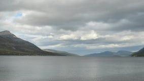 Capa rápida de la nube sobre las montañas majestuosas y el fiordo azul metrajes