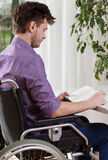 Capable disabled man reading a book Stock Photos