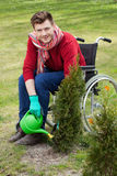Capable disabled watering flowers Royalty Free Stock Images