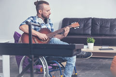 Capable handicap playing musical instrument in the studio. Full of concentration. Involved talented young handicap sitting on the wheelchair in the studio and Royalty Free Stock Image