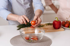 Capable son helping his aged mother cooking in the kitchen Stock Images