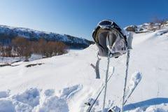 Capacete, óculos de proteção Polos e esquis na montanha nevado Fotos de Stock Royalty Free