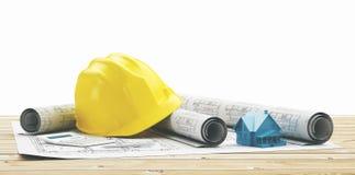 Capacete amarelo com projetos imobiliários e casa imagens de stock