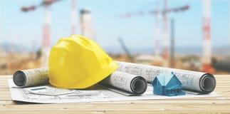 Capacete amarelo com projetos imobiliários e jarda com guindaste Imagens de Stock