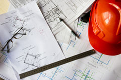 Capacete da construção na tabela com esboços dos desenhos fotos de stock