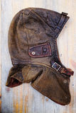 Capacete de couro do vintage sobre o fundo de madeira Imagens de Stock Royalty Free