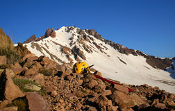 Capacete de escalada amarelo e machado de gelo vermelho, encontrando-se em uma rocha nas montanhas Imagens de Stock