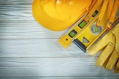 Capacete de madeira da construção do medidor do nível da construção das luvas da segurança sobre Foto de Stock
