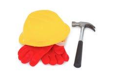 Capacete de segurança amarelo com luvas protetoras e martelo Fotografia de Stock Royalty Free