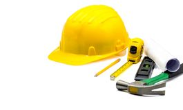 Capacete de segurança amarelo com modelos e lápis, fita métrica, martelo, nível de bolha da construção isolado no fundo branco, e foto de stock royalty free