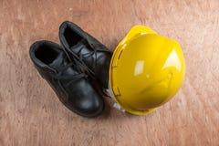Capacete de segurança amarelo e botas de couro, equipamento de proteção na indústria da construção civil imagem de stock royalty free