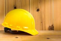 Capacete de segurança amarelo no assoalho de madeira com fundo de madeira da parede, Foto de Stock