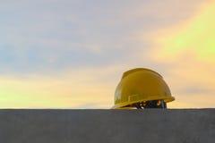 Capacete de segurança amarelo no fundo do por do sol da cidade Imagens de Stock Royalty Free