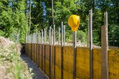 Capacete de segurança amarelo que pendura dos painéis de madeira apoiados fotografia de stock royalty free