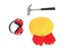 Capacete de segurança com luvas, capas protetoras para as orelhas e martelo no branco Fotografia de Stock