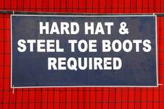 Capacete de segurança e sinal exigido botas fotos de stock