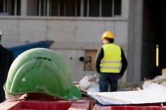 Capacete de segurança verde da segurança no primeiro plano Trabalhador da construção no fundo fotografia de stock