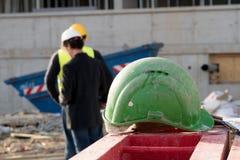 Capacete de segurança verde da segurança no primeiro plano Trabalhadores da construção no fundo imagens de stock