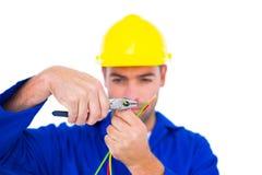 Capacete de segurança vestindo do eletricista ao cortar o fio com alicates Imagens de Stock