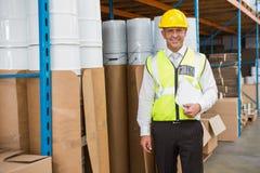 Capacete de segurança vestindo do gerente do armazém que guarda a prancheta Imagens de Stock
