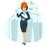Capacete de segurança vestindo do trabalhador da construção da mulher que guarda modelos e apontar da prancheta Imagem de Stock Royalty Free