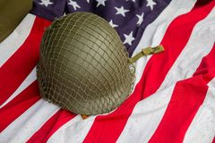 Capacete do ` s do soldado e os tempos da segunda guerra mundial e da bandeira dos E.U. imagens de stock