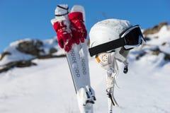 Capacete e óculos de proteção com esquis e Polos no monte Fotografia de Stock Royalty Free