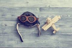 Capacete e avião de madeira o conceito de conquistar o céu Imagens de Stock Royalty Free