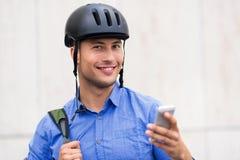 Capacete vestindo da bicicleta do homem fotografia de stock