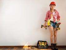 Capacete vestindo da mulher, toolbelt aproximadamente para furar a parede Fotografia de Stock Royalty Free