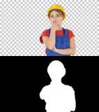 Capacete vestindo de pensamento do construtor da mulher do trabalhador da construção, Alpha Channel imagens de stock
