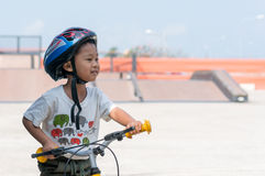 Capacetes vestindo do rapaz pequeno que livram a bicicleta Foto de Stock