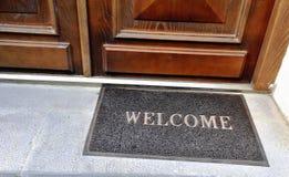 Capacho com sinal bem-vindo na entrada Fotografia de Stock