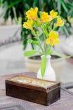 Capacidad del azúcar del viejo estilo con la flor amarilla en florero en la tabla de madera imagen de archivo