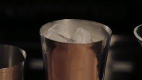 Capaciteit voor een cocktail met ijs bij de bar stock footage