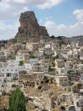 Capadoccia的典型村庄与一个奇怪的形式岩石的在距离在土耳其 免版税库存照片