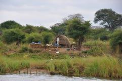 Capanna africana accanto al fiume Fotografie Stock