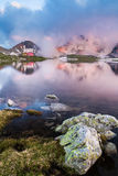 Capanna in alta montagna con il lago Fotografia Stock Libera da Diritti