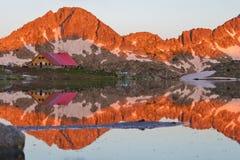 Capanna in alta montagna con il lago Immagini Stock Libere da Diritti