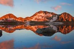 Capanna in alta montagna con il lago Immagini Stock