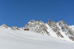 Capanna del chalet in montagne nevose e rocciose, alpi svizzere Fotografie Stock Libere da Diritti