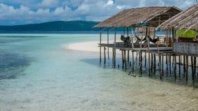 Capanna dell'acqua dell'alloggio presso famiglie sull'isola di Kri - di Sandy Bank Raja Ampat, Indonesia, Papuasia ad ovest Immagini Stock