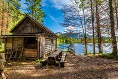Capanna di legno della foresta nelle alpi nel lago Fotografia Stock Libera da Diritti