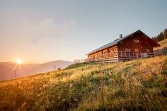 Capanna di legno della montagna al tramonto nelle alpi di estate Fotografie Stock Libere da Diritti