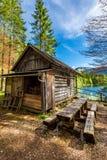 Capanna di legno della vecchia foresta nelle alpi nel lago Immagine Stock Libera da Diritti