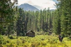 Capanna di legno nelle montagne di Altai e nelle coppie i turisti Immagine Stock