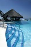 Capanna e barra di Tiki dalla piscina dell'albergo di lusso Immagini Stock