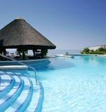 Capanna e barra di Tiki dalla piscina dell'albergo di lusso fotografia stock