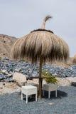 Capanna, ombrello da paglia e sedie sulla spiaggia vulcanica della sabbia nera in Tenerife, isole Canarie immagine stock libera da diritti